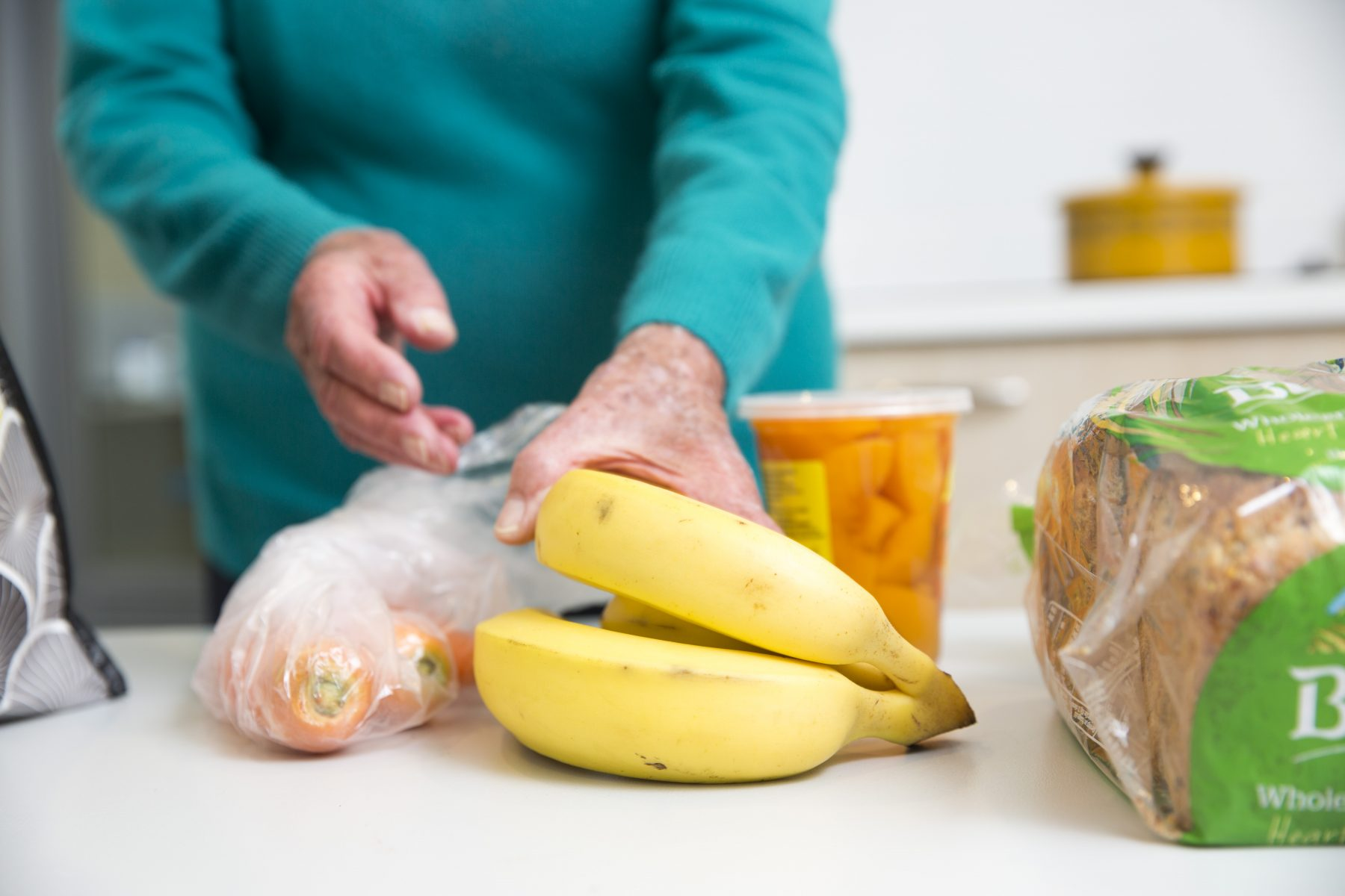 older person putting away grocery shopping