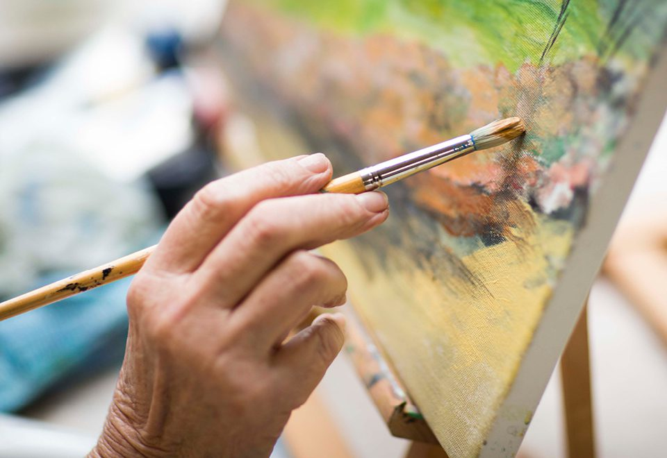 older person paining at ACH art group