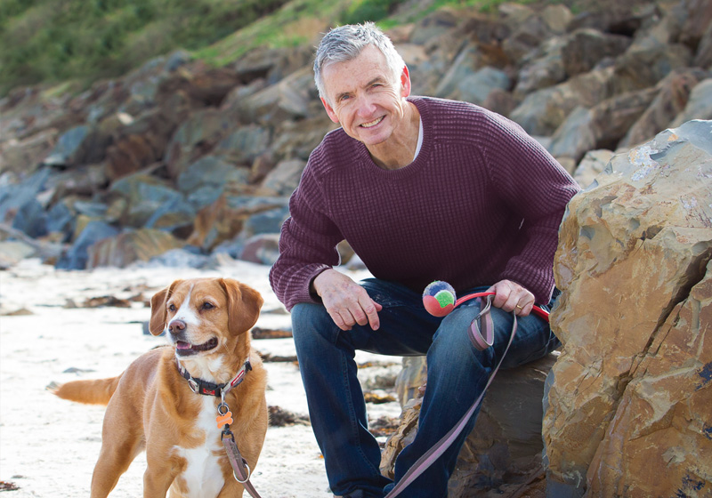 Bruce McAvaney with his dog on the beach