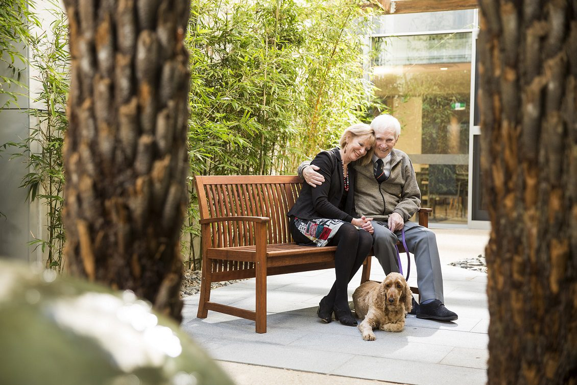 older couple with dog sitting on park bench