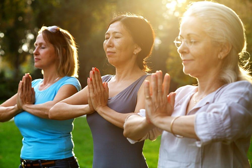 Women doing yoga in the park enjoying retirement living lifestyle