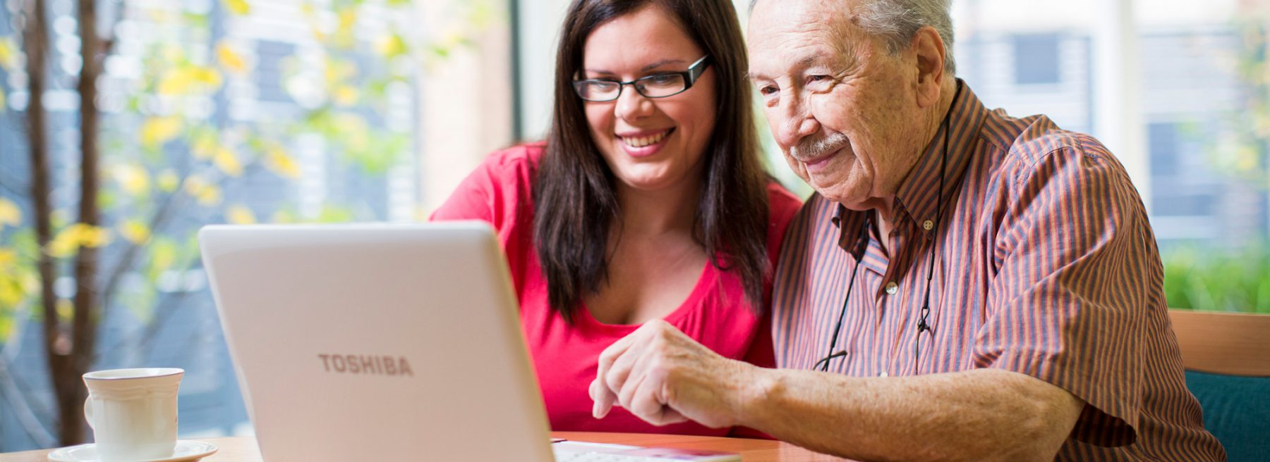 ach group aged care resident with younger woman working on computer