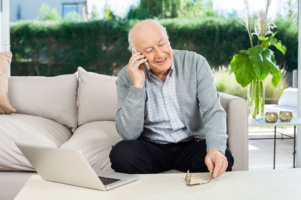 Happy,Senior,Man,Answering,Smartphone,While,Sitting,On,Couch,At