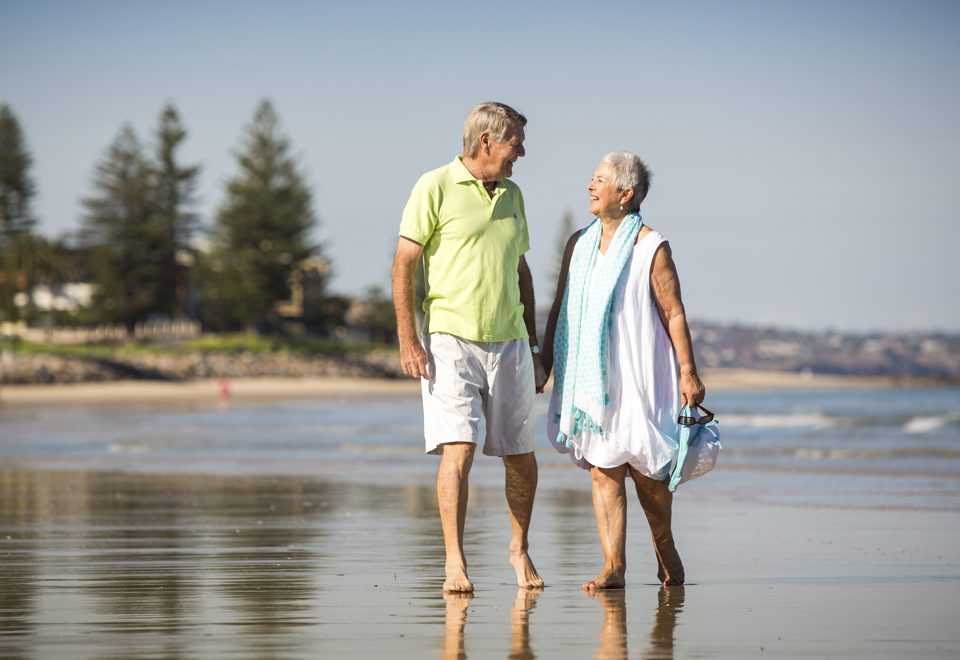 Old couple taking a walk at the beach and getting active