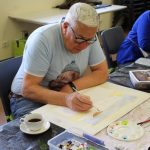 man painting in ach art class