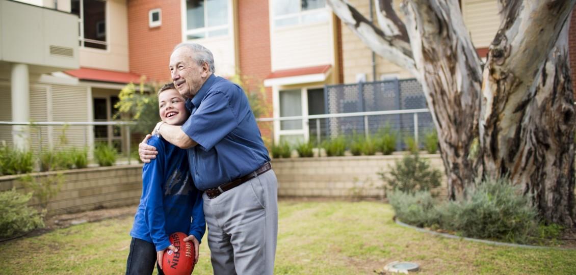 older man hugging boy at ach group retirement living unit