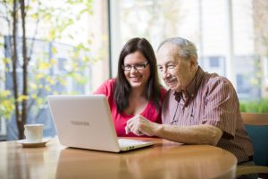 older adelaide retirement living resident and younger woman working on computer