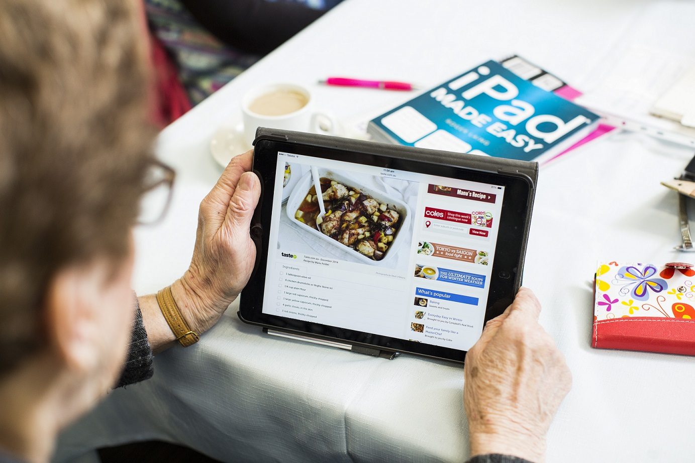 older person using ipad to research recipes