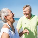 two older people laughing on the beach
