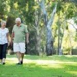 two older people walking in park