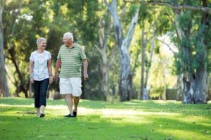 two older people walking in park