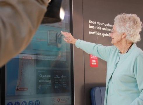 older woman booking driverless bus in glenelg