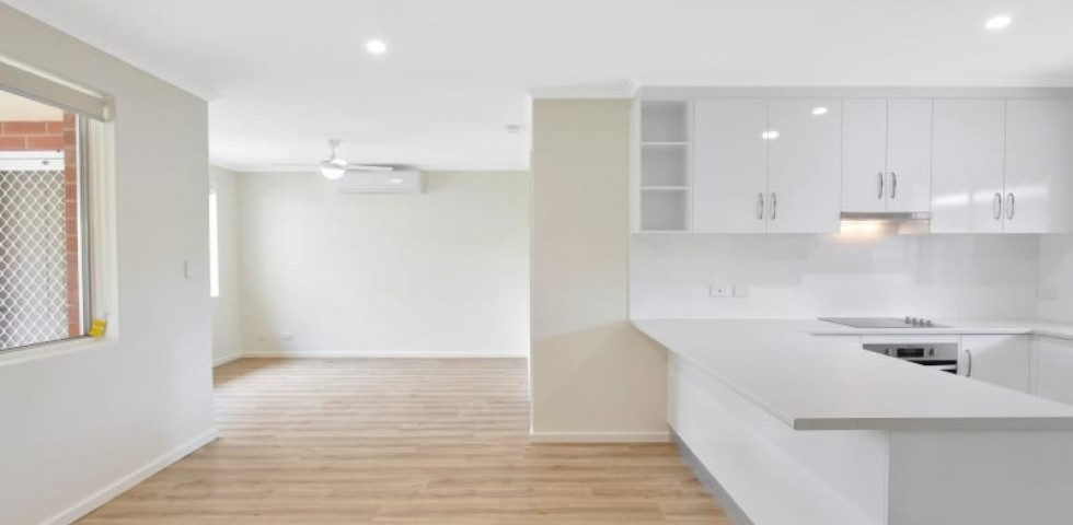 ACH Group Campbelltown retirement living unit kitchen with hard wood floor