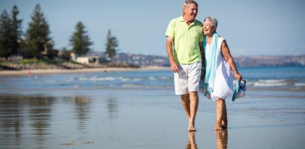 two older people walking on glenelg beach
