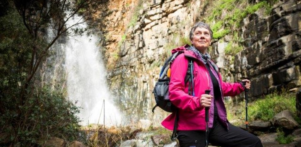 older woman hiking with waterfall in background